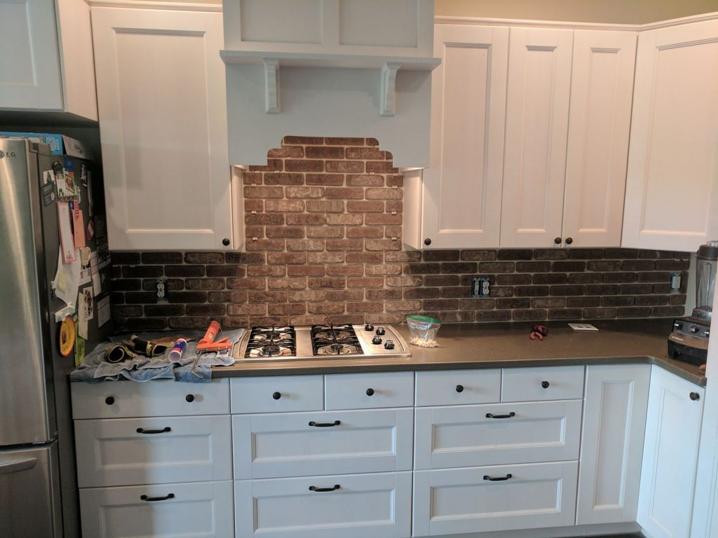 Ikea kitchen cabinets with custom range hood and brick backsplash